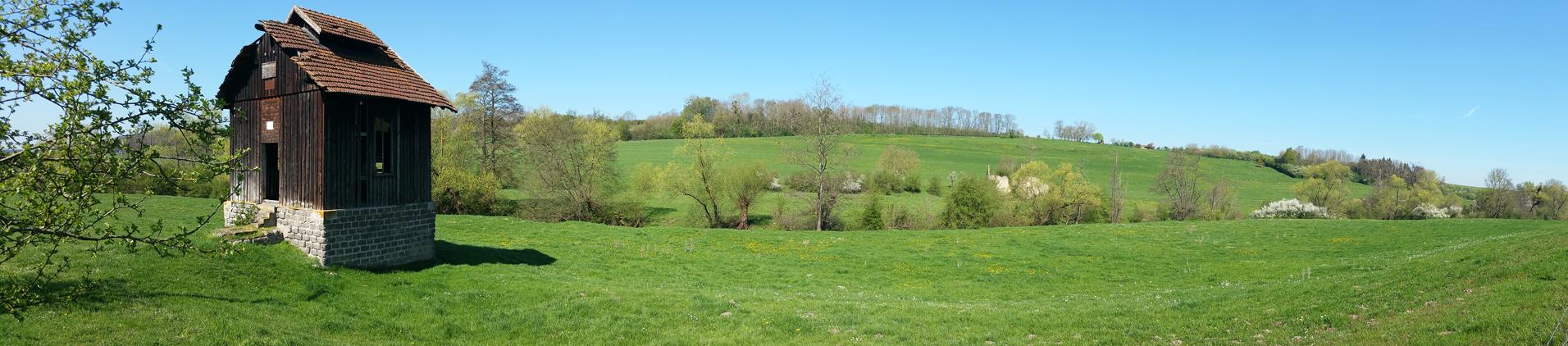 Le chevalement de Lenoncourt, petite cabane de bois à double toiture, dans un grand paysage verdoyant avec colline